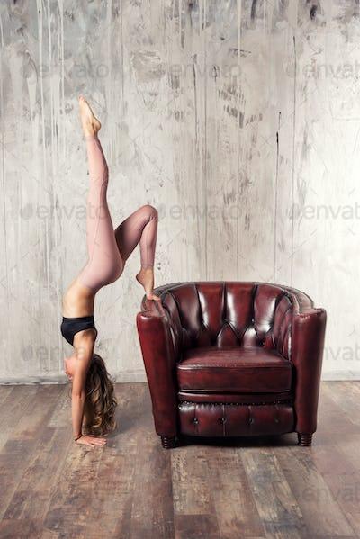 Fit woman doing Adho mukha vrkasana yoga pose