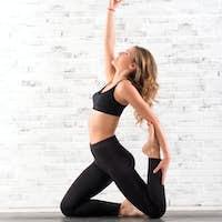 Fit woman doing ardha dhanhrasana yoga pose