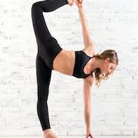 Fit woman doing ardha chandra chapasana yoga pose