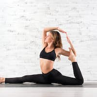 Young fit woman doing yoga pose on mat