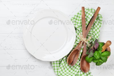 Empty plate with utensils and herbs