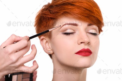 The artist is applying eyeshadow on her eyebrow with brush. The