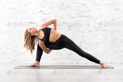 Fit woman doing utthita parsvakonasana yoga pose