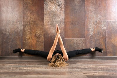 Fit woman exercising yoga on wooden floor