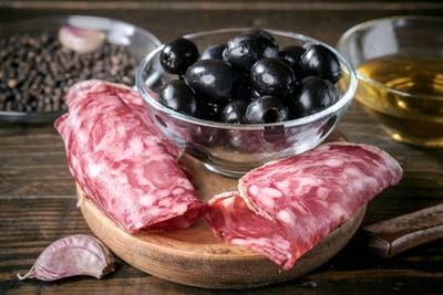 slices of Iberian sausage and bowl of black olives on wooden board