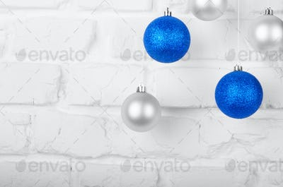 Christmas blue and silver balls on white brick wall holiday back