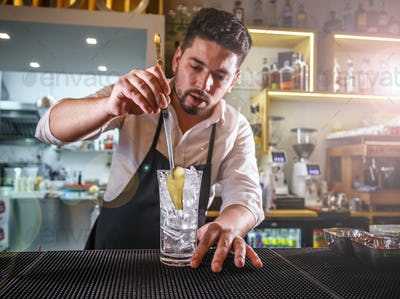 Bartender adding ginger into a glass