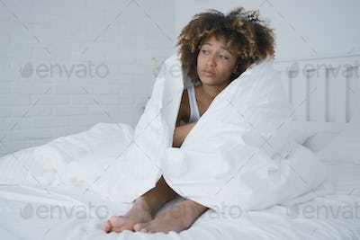 Sad woman wrapping in blanket
