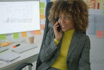 Cheerful elegant worker talking on phone