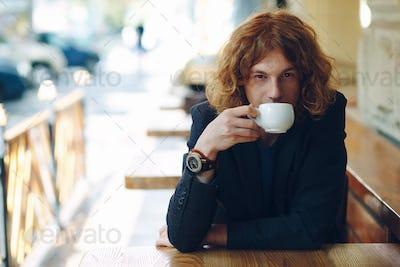 Portrait fashionable man drinking coffee