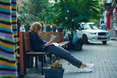 Hipster lying on bench reading newspaper