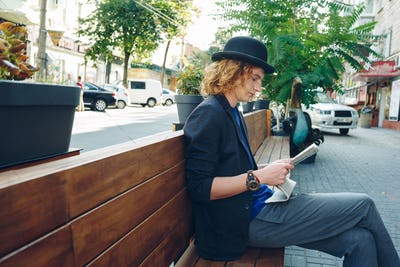 Curly hipster on wooden bench in the city