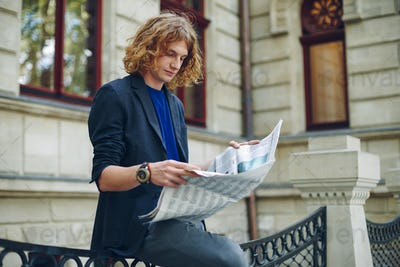 Young reddish man reading newspaper near old style building