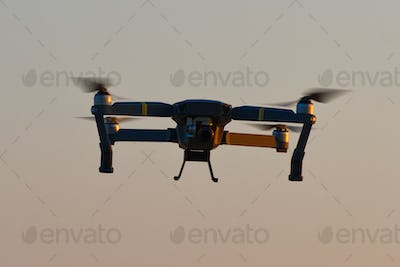 Drone quad copters with high resolution digital camera flying aerial over sunset orange sky