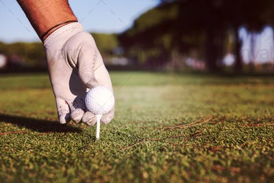 close up of golf players hand placing ball on tee