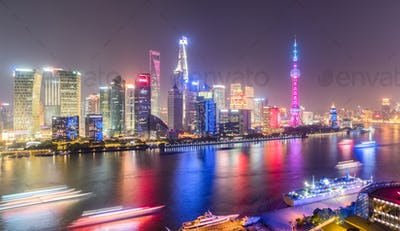 shanghai skyline in evening, light trails of pleasure boat on huangpu river