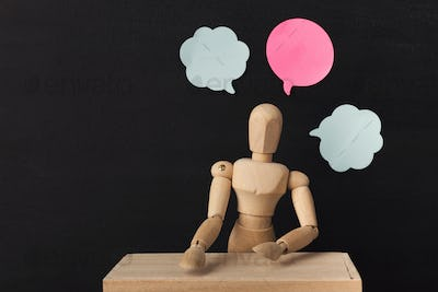 Wooden man mannequin with blank speech bubbles