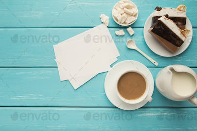 Cup of coffe and cake on turquoise rustic table, top view