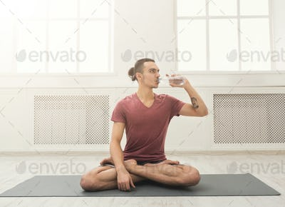 Fitness man drinking water at gym
