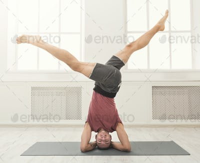 Young flexible man standing on hands