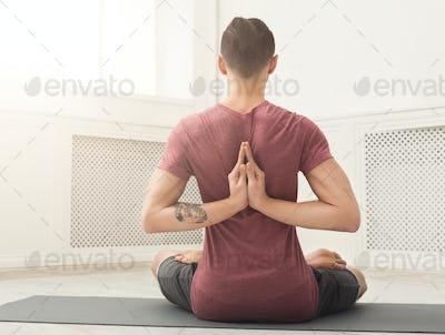 Young man practicing yoga, Reverse Prayer Pose