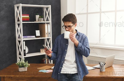 Relaxed young businessman using mobile in office