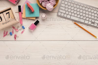 Desk with keyboard, stationery and sweets, top view