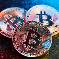 Three bitcoin coins in a colorful lighting.