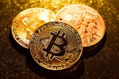 Three golden bitcoin coins on black background.