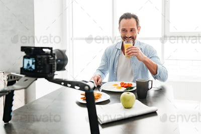 Handsome mature man recording video food blog