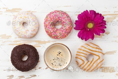Coffee cup, donuts and gerbera flower