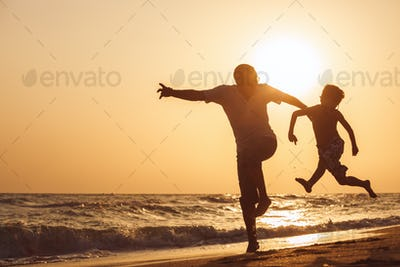 Father and son  playing on the beach at the sunset time.