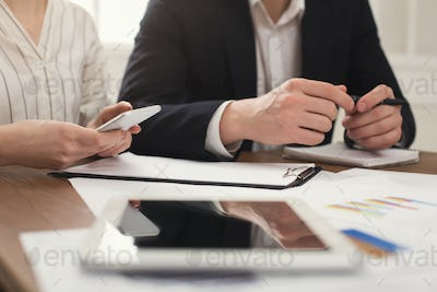 Business colleagues using smartphone and working with documents