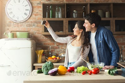 Happy couple cooking and taking selfie in kitchen