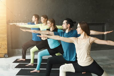Young women and men in yoga class, doing stretching exercises