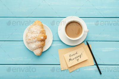 Cup of coffe and croissant on turquoise rustic table, top view