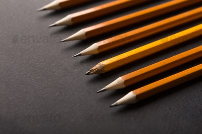 One old and plenty of new pencils on black background