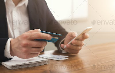 Man's hands holding a credit card and using smartphone