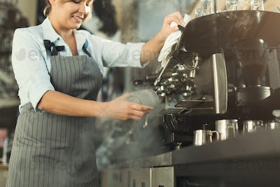 Experienced barista making coffee in professional coffee machine