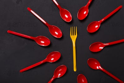 Top view on plastic fork and spoons on black background