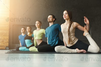 Young women and men in yoga class, mermaid pose stretching