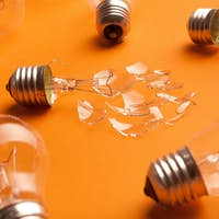 Whole and broken light bulbs on yellow background