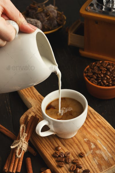Woman pouring milk into black coffee on vintage wooden board