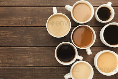 Different types of coffee in cups on wooden table, top view
