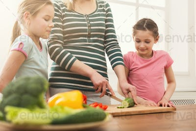 Woman with her daughters cooking salad
