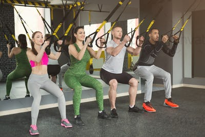 Group performing TRX suspension training in gym