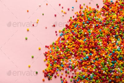 Colorful sprinkles scattered on pink background