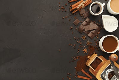 Top view on various coffee cups, scattered beans and spices, bac