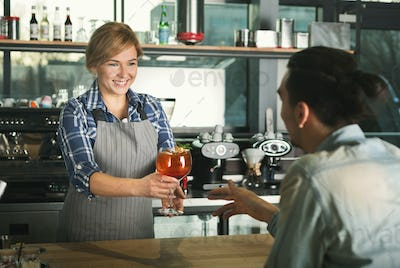 Smiling barista taking payment from client