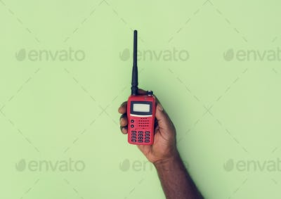 Hand holding walkie-talkie isolated on background